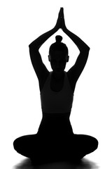 Silhouette of young woman in yoga pose