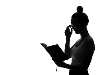 Silhouette of young woman reading book against white background