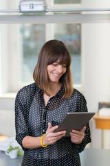 lächelnde frau im büro schaut auf tablet-pc