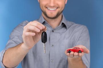 Happy man holding car keys on blue background.