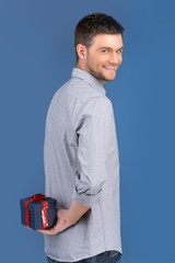 side view of smiling guy holding gift in blue box.