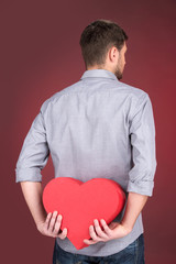 Portrait of young man holding heart shape over red background.