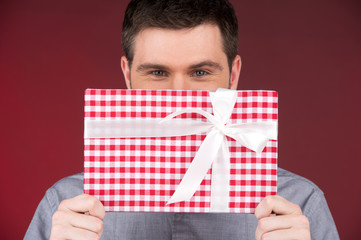 Present gift in hands of smiling man covering half face.