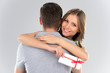 Young couple hugging with wrapped present.