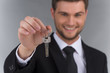 Businessman in tie holding key with focus on key.