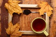 Autumn (fall) cup of tea and colorful leaves over rustic wooden