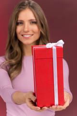 Gorgeous cute young woman holding present box.
