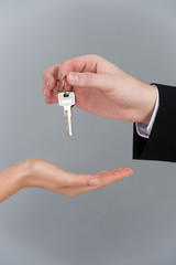 Male hand holding key and handing it woman.