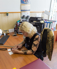 Attractive secretary talking on the phone while writing sms