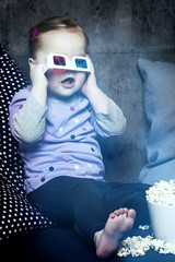Young girl in 3D glasses with popcorn
