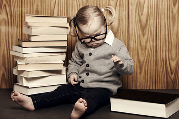 Young girl in glasses sitting by pile of books