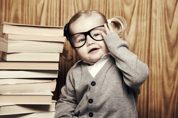 Young girl in glasses next to stack of books