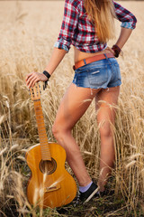 beautiful sexy girl with guitar in the field, close up