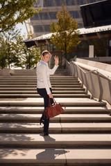 Junge Frau geht Treppen hinauf und winkt zum Abschied