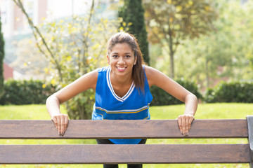 Smiling athletic woman doing pushups on the bench.
