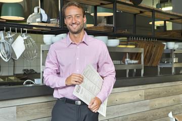 Smiling business owner holding menu in restaurant