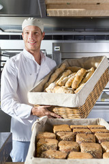 Smiling baker holding basket of bread in bakery kitchen