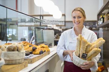 Smiling baker holding basket of bread in bakery