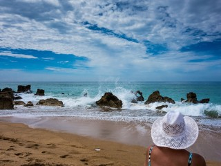 Junge Frau lauscht dem Meeresrauschen