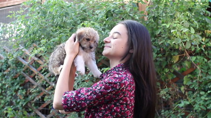Teenage girl playing with puppy in the garden