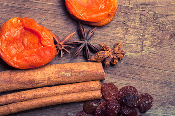 Raisins, cinnamon, anise and dried apricots lying on an old wood