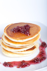 Pancakes with raspberry jam on a light background
