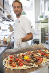 Chef displaying pizza on spatula in kitchen