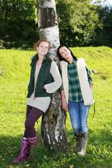 Zwei Freundinnen lehnen an Birke
