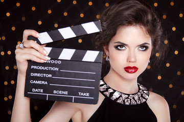 Fashion elegant woman with sexy red lips holding cinema clap. Su