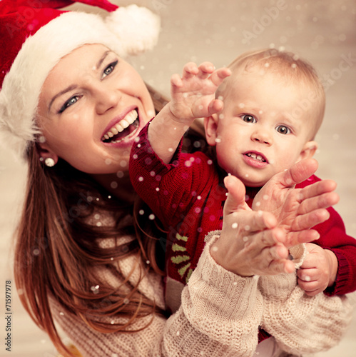 canvas print picture Happy family looking at falling snowflakes celebrating Christmas