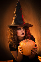 Woman dressed like a witch. She is holding a pumpkin in hands.