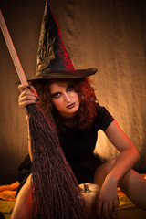 Woman dressed like a witch with broom.