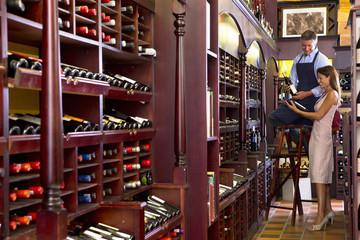 Worker on ladder assisting customer in wine shop