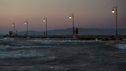 People on pier in the windy evening