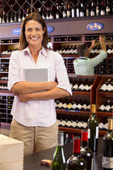 Smiling business owner with digital tablet in wine shop