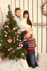 parents and kid near Christmas tree.