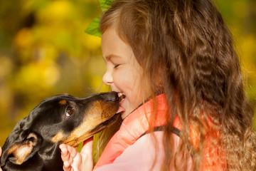 Little kid kissing dachshund puppy.