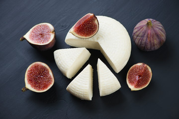 Sliced fig fruits and cheese on a black wooden surface