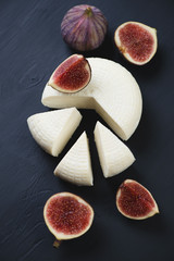 Sliced cheese and figs, black wooden surface, high angle view
