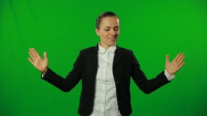 Young pretty woman presents something on a green screen.FULL HD
