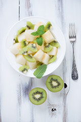 Above view of melon and kiwi salad in a glass plate, studio shot