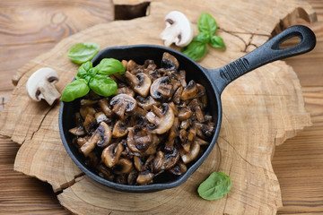 Frying pan with roasted champignons, rustic wooden background