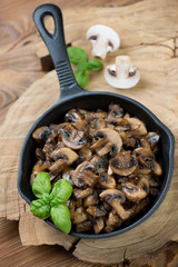 Cast-iron frying pan with fried champignons, high angle view