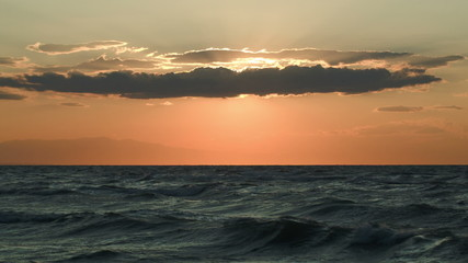 Rough sea and evening sun hidden with cloud