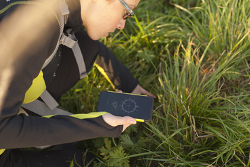 Woman with backpack looking the geocache with digital compass