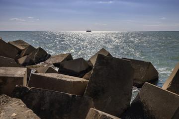 Italy, Sicily, Scoglitti, fishing boat and concrete blocks