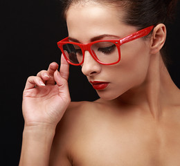 Beautiful makeup woman in red eyes glasses looking down. Closeup