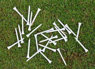 White wood tee on grass.