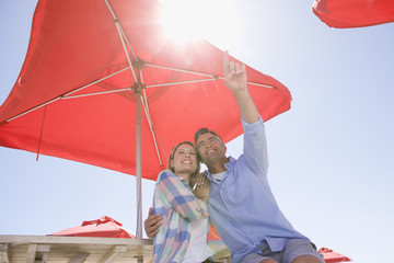 Smiling couple pointing up under umbrella at table
