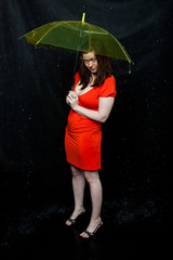 girl wearing red dress stands under an umbrella